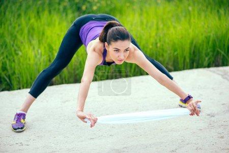 Photo pour Exercices de jeune femme sportive attrayante séance d'entraînement dans le parc avec serviette blanche. Fond naturel. En t-shirt violet. Regardez vers l'avant.Sport - image libre de droit