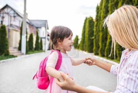 Photo pour Fille heureuse petite fille et jolie mère embrassant l'autre sur le trottoir sur la rue. Maman a rencontré l'enfant après l'école maternelle à la maison à l'extérieur. Maman et les enfants sont amusent. Concept de la fête des mères. - image libre de droit