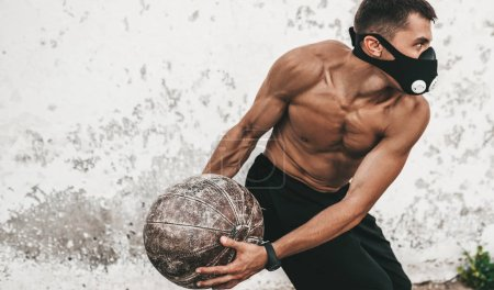 Photo pour Horizontale de l'image de faire mâle musculaire fitness exercices avec médecine-ball en masque sur fond béton extérieur. Copiez l'espace pour la publicité. Torse nu sportif faisant d'entraînement - image libre de droit