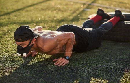 Photo for Young Caucasian fitness muscular male in mask to increase load on breathing muscles doing push-ups exercises on tire outdoors. Copy space. Shirtless sportsman doing workout on stadium. - Royalty Free Image