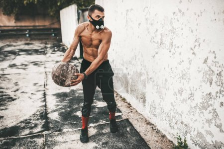 Photo for Fitness athlete male doing exercises with medicine ball in mask on concrete background outdoor with copy space for your advertising. Caucasian shirtless sportsman doing workout - Royalty Free Image