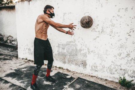 Photo pour Horizontale de l'image de musculaire mâle faire des exercices avec médecine-ball en masque sur fond béton extérieur avec espace copie pour votre publicité. Torse nu sportif faisant d'entraînement. - image libre de droit