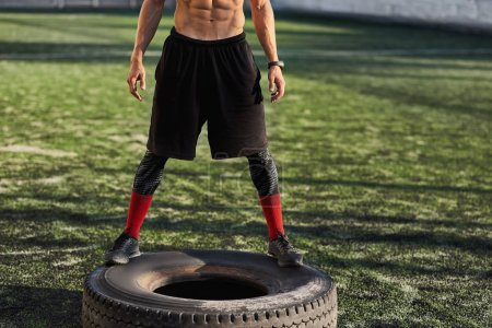 Photo for Horizontal cropped body shot of muscular male tire-flip exercises outdoors in stadium on green grass. Copy space for your advertising information. Shirtless sportsman doing workout. Sport and people - Royalty Free Image