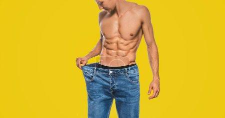 Photo pour Image studio horizontale de jeune homme en forme caucasien portant un gros jean bleu après le régime alimentaire, montrant un torse sexy. Homme attrayant posant sur fond jaune après avoir perdu du poids. Espace de copie. Mode de vie sain - image libre de droit