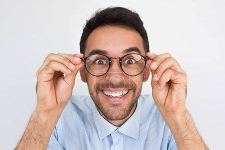 Photo for Closeup shot of amazed young European handsome male, looking through round spectacles, touches rim of glasses, smiling with healthy toothy smile posing in studio. People, emotion and lifestyle concept - Royalty Free Image