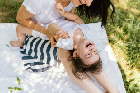 Photo for Cropped image of beautiful woman wearing striped skirt help her daughter to stand up in the park. Cute mother and her little kid playing together outdoors. Happy family. Happy Mother's Day. Motherhood - Royalty Free Image