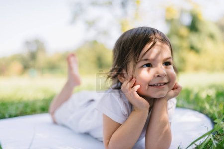 Photo for Horizontal portrait of happy smile toddler girl have fun outdoor in the park, sitting on a white blanket. Positive expression of a child. Adorable kid on nature sunlight. Childhood concept. - Royalty Free Image