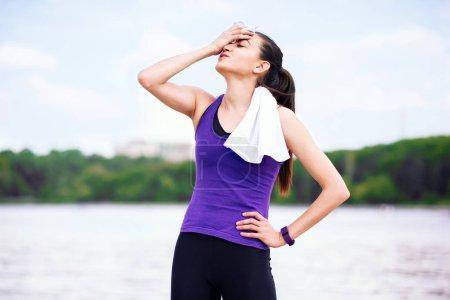 Photo pour Pause et loisirs avant ou après l'entraînement et la course dans le parc. Femme séduisante sur t-shirt violet, sur fond nature. Le sport - image libre de droit