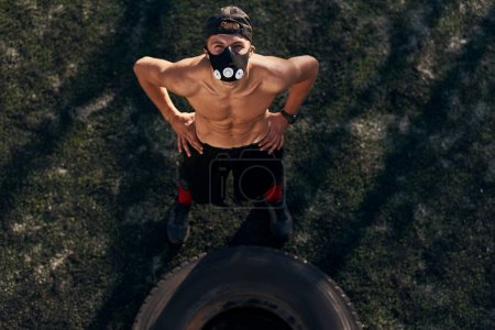 Photo for View from above of muscular young male with mask looking at the camera while doing exercises with big tire outdoors in stadium. Shirtless sportsman doing hard workout, healthy lifestyle. People, sport - Royalty Free Image