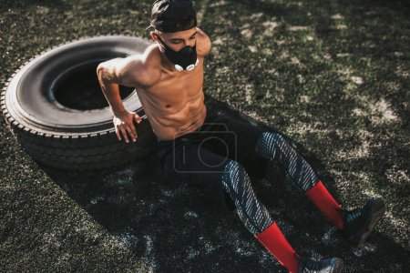 Photo for Caucasian fitness muscular male sitting in mask to increase load on breathing muscles doing exercise for triceps on tire outdoors. Copy space. Shirtless sportsman doing workout crossfit - Royalty Free Image