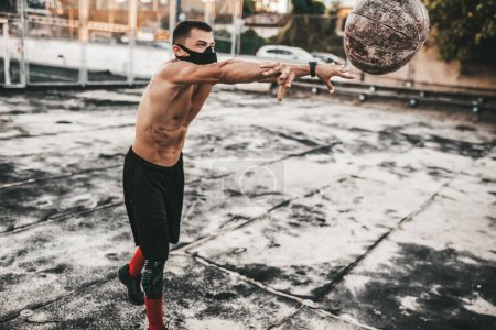 Photo pour Image de l'athlétisme masculin faisant des exercices avec médecine-ball en masque sur fond béton extérieur avec espace copie pour votre publicité. Caucasien sportif torse nu faisant d'entraînement - image libre de droit
