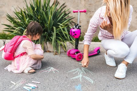 Photo for Image of happy little girl wears pink dress and mother drawing with colorful chalks on the sidewalk. Caucasian female play together with kid preschooler with backpack outdoor. Mom and child activity - Royalty Free Image