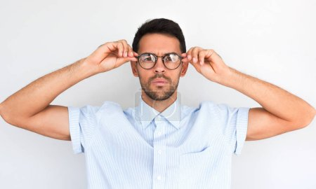 Photo for Unshaven handsome serious male touches rim of spectacles, has bad eyesight, posing against white studio background. Caucasian confident young man worker with glasses in blue shirt. People, business - Royalty Free Image