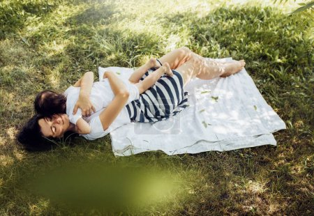 Photo for Top view of cheerful Caucasian mother and her little daughter playing outdoors on grass after picnic. Cute mom and her cheerful child have fun in the park. Motherhood and childhood concept. - Royalty Free Image