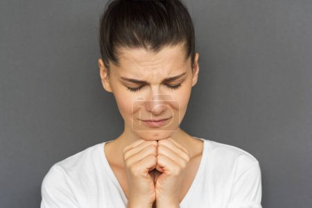 Photo for Closeup portrait of praying young female with dark hair holding her hands together at the chin, being concentrated on her wish. Pretty woman in casual clothes praying for good luck and success on gray - Royalty Free Image