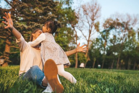 Photo for Joyful happy girl kid playing with her mother outdoor. Portrait of happy woman and her cute child embracing in the park. Happy family emotion. Happy Mother's Day. Motherhood and childhood. - Royalty Free Image
