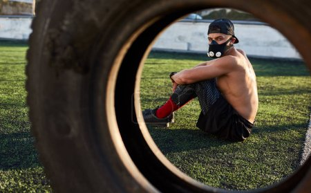 Photo for Fitness muscular male in mask to increase load on breathing muscles sitting after exercises on tire outdoors. Copy space for your text. Shirtless sportsman doing workout on stadium. - Royalty Free Image