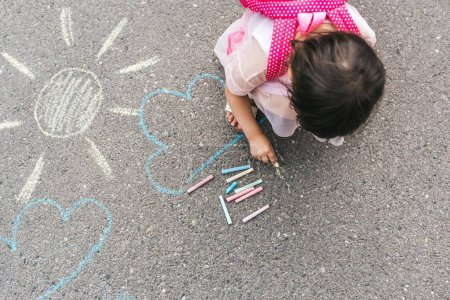 Photo for Top view image of happy little girl wears pink dress and backpack drawing with colorful chalks on the sidewalk. Cute child preschooler play outdoor on pavement. Toddler educational activity outside. - Royalty Free Image