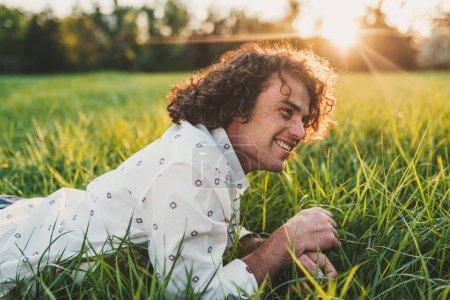 Foto de Toma exterior horizontal de estudiante modelo masculino joven guapo alegre con pelo rizado, sonrisa, relajarse en el verde césped del parque. Copiar espacio para publicidad. Concepto de estilo de vida y personas. - Imagen libre de derechos