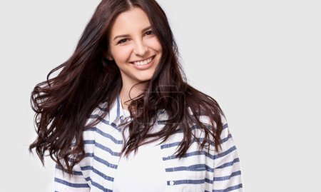 Photo for Closeup indoor portrait of beautiful brunette young woman with long hair smiling cheerfully. Charming female smile broadly showing her white healthy teeth to camera while feeling happy and carefree - Royalty Free Image