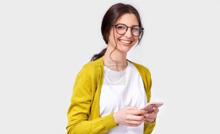 Photo pour Européenne belle brune jeune femme souriante à l'aide de téléphone portable, messagerie à son amie. Heureuse femme bavardant avec son petit ami par l'intermédiaire de téléphone intelligent, en regardant la caméra. Gens, technologie, émotion - image libre de droit