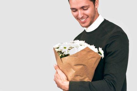 Photo pour Bel homme heureux souriant offrant un bouquet de fleurs blanches. Modèle masculin attrayant avec un bouquet de fleurs à préparer pour une date avec une copine. Saint-Valentin. Concept de la fête des mères - image libre de droit