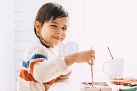 Photo for Side view portrait of cute smiling little girl painting and drawing with brush and watercolor on white desk at home. Pretty preschooler kid drawing with pencil. People, childhood and education concept - Royalty Free Image
