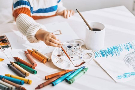Photo for Top view cropped image of cute little girl painting and drawing with brush and watercolor on white desk at home. Pretty preschool kid draws in the kindergarten. People, childhood and education concept - Royalty Free Image