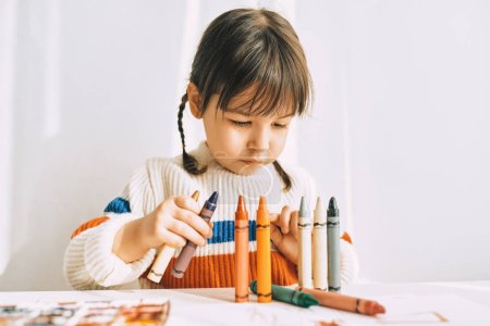 Photo for Portrait of creative cute little girl playing with oil pencils, sitting at white desk at home. Pretty preschool kid draws with pencils. People, childhood and education concept - Royalty Free Image