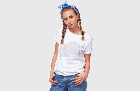 Photo pour Charmante belle jeune femme portant des t-shirt blanc, bandeau bleu avec les mains dans les poches, à la recherche à la caméra, isolée sur fond blanc studio - image libre de droit