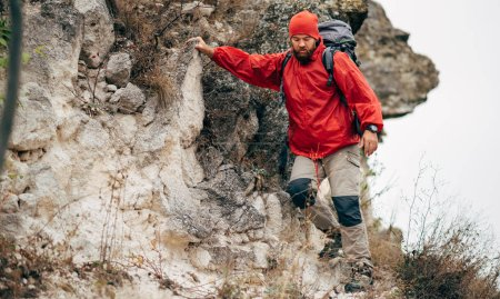 Photo for Image of young male hiking in mountains wearing red clothes exploring new place. Traveler man trekking and mountaineering during his journey. Travel, people, sport and healthy lifestyle concept - Royalty Free Image