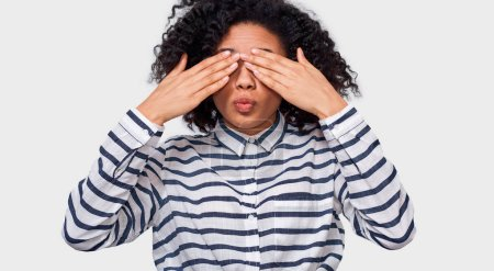 Photo for Good-looking stylish African American young woman in striped shirt, covering eyes with palms and making air kiss, waiting to be kissed. Playful dark-skinned  female playing hide, seek and peek a boo. - Royalty Free Image