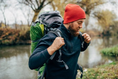 Photo for Side view shot of young hiker male hiking in mountains with travel backpack. Traveler bearded man relaxing after mountaineering standing near to a river. Travel, people and healthy lifestyle concept - Royalty Free Image