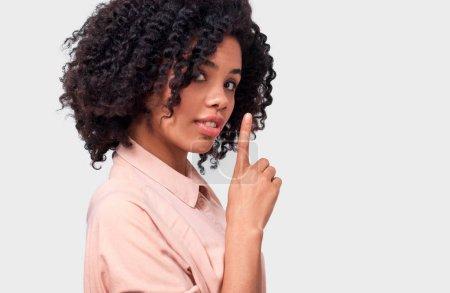 Photo pour Confidentielle jeune femme afro-américaine habillé en chemise rose tenant le doigt sur les lèvres, demandant de garder le silence sur le mur blanc. Belle foncé femelle dénudées se tourne vers la caméra demande à être calme - image libre de droit