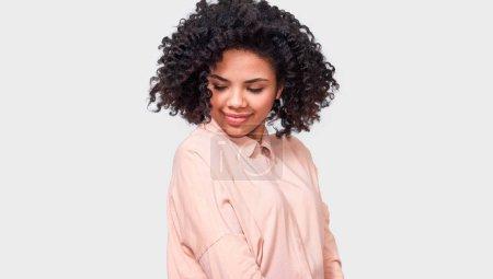 Foto de Ensueño piel oscura mujer sonriendo ampliamente con los ojos cerrados, con camisa beige, disfrutar de buen tiempo, posando contra la pared del estudio blanco. Concepto personas, emociones, éxito y felicidad - Imagen libre de derechos
