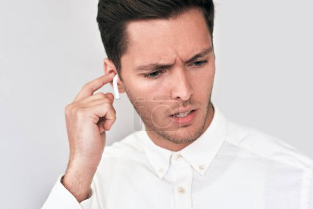Photo for Closeup portrait of sad young handsome man wearing white shirt and speaking with a friend using wireless earphones. Serious businessman using wireless earbuds during conversation. People, technology - Royalty Free Image