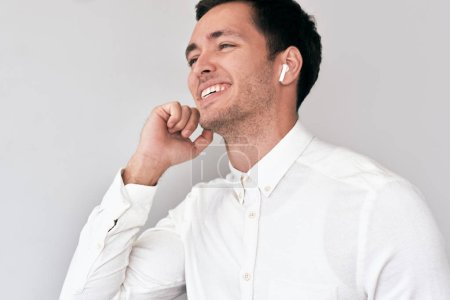 Photo for Young man smiling, having a call via wireless earphones with a colleague isolated on white wall. Caucasian businessman wearing white shirt, using wireless earbuds for communication. Technology, people - Royalty Free Image