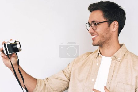 Photo for Side view portrait of cheerful young man freelancer taking selfie over white studio background and looking to his digital camera. Young male smiling and wearing eyewear making self portrait, blogging - Royalty Free Image