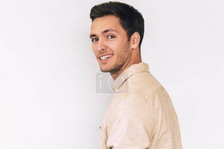 Photo pour Vue coup de beau jeune homme souriant et vêtu d'une chemise beige décontractée, à la recherche à la caméra et le posant sur fond de studio blanc de l'arrière. Concept d'émotion de personnes - image libre de droit