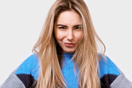 Photo for Closeup portrait of beautiful young woman frowning her face, wearing sweater, looking directly to the camera. - Royalty Free Image