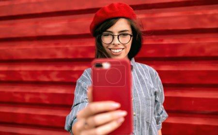 Photo pour Portrait urbain de la jeune femme brune souriant largement, prenant l'autoportrait, portant une chemise bleue, un chapeau de béret rouge et des lunettes, posant sur un mur de fond rouge. Étudiante femme faire selfie sur téléphone portable - image libre de droit