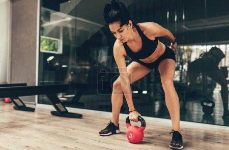 Photo pour Jeune femme de fitness faisant de l'exercice de swing avec une kettlebell rouge dans le cadre d'un entraînement de fitness dans la salle de gym . - image libre de droit