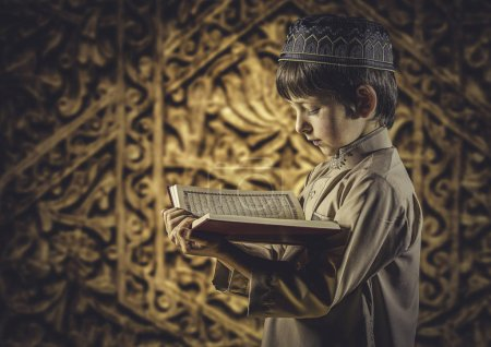 Photo for Little Muslim boy with Holy Islamic Book Quran - Royalty Free Image