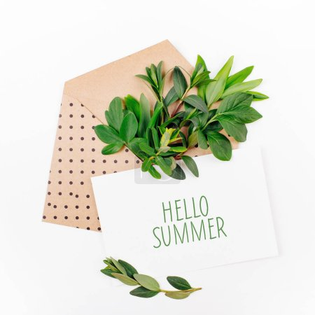 Photo for Styled desk with envelope, blank card, composition of green leaves and gold office stuff. Flat lay. - Royalty Free Image