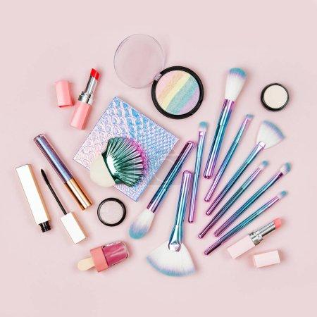 Photo pour Pinceaux de maquillage fard à paupières, poudre et autres produits cosmétiques sur fond rose pastel de couleur mode holographique. Vue plate Lapointe, top - image libre de droit