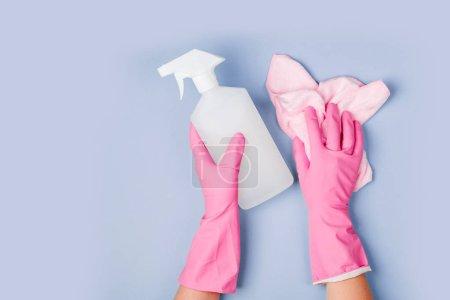 Photo pour Les mains dans des gants de caoutchouc tenant nettoyant spray et microfibre chiffon - image libre de droit