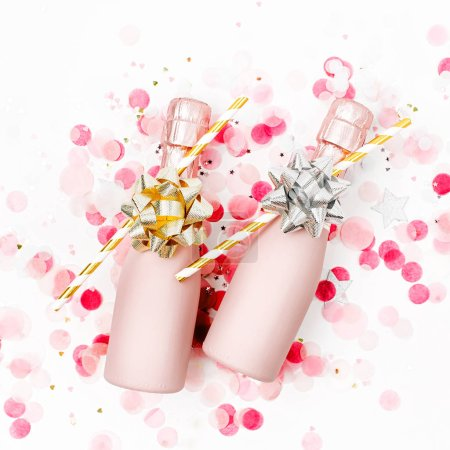 Photo for Pale Pink Mini bottles of champagne with confetti on white background - Royalty Free Image