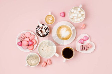 Various kinds of coffee in cups of different size with candys and macaroons on pale pink background.  Coffee  Time concept.  Flat lay, top view