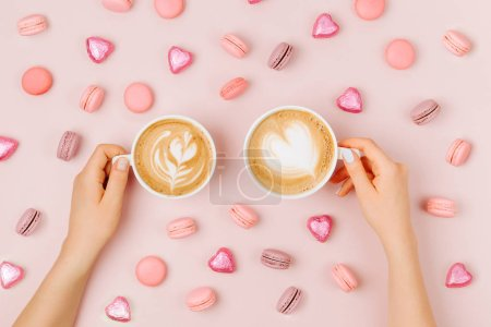 Female hands hold cappuccino art heart shape in a coffee cup on pale pink background.  Love concept.  Flat lay, top view