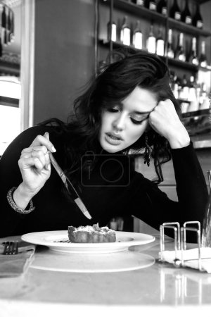 Photo for Fashion photo of beautiful young woman with dark curly hair in elegant dress sitting in elegant restaurant, eating delicious cake - Royalty Free Image
